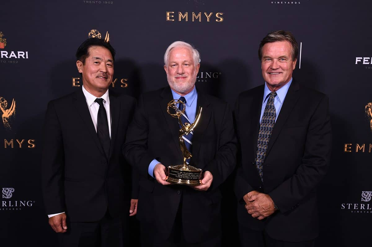 Miles Shozuya, from left, Gordon Tubbs, and Chuck Lee pose with the Engineering Emmy Award for Fujifilm Fujinon 4K Zoom Lenses
