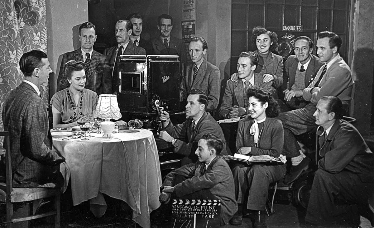 <em>Vengeance is Mine</em>... using an old Vinten camera. Valentine Dyall was the star of the picture (seated in front of the camera), with cinematographer Jimmy Wilson (second row, first from left). George Bull (gaffer, second row second from left), Charlie Parkhouse (sound mixer, to the right of the lamp), Bill Oxley (camera operator) and the focus puller Mo Pierrepoint
