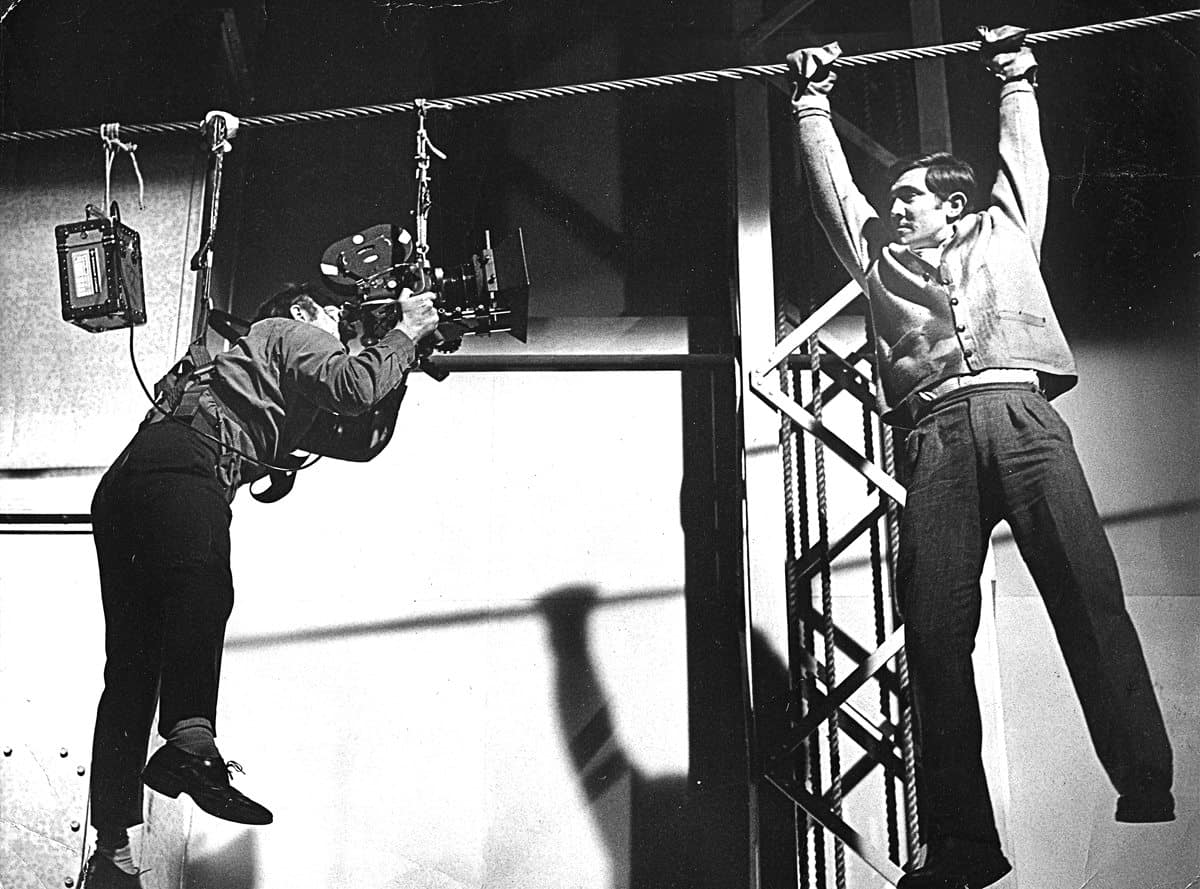 <em>On Her Majesty's Secret Service</em>... in the cable car winding house of Blofeld's Piz Gloria lair. The sequence was actually filmed on a mechanism designed by SFX supervisor John Stears on a stage at Pinewood, so Mills was not quite so high off the ground. But being winched towards the giant cogwheels at 15mph he still needed to be confident that the cable would stop at the right time!