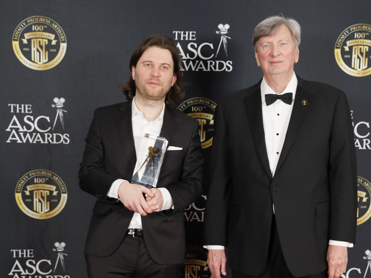 <em>Cold War</em> camera operator, Ernest Wilczynski, with the ASC Award for DP Lukasz Zal, alongside Academy President John Bailey