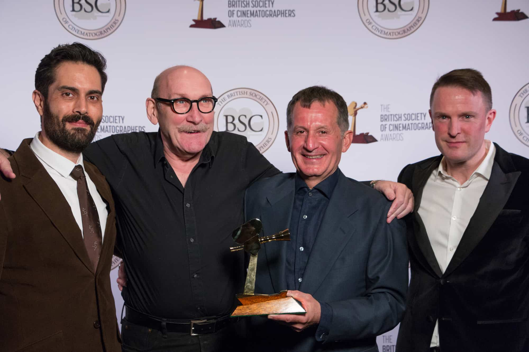 Collaborators from <em>1917</em> accept the Feature Film award on behalf of Roger Deakins - including camera operators Charlie Rizek (far left) and Peter Cavaciuti (second right), plus gaffer John 'Biggles' Higgins (second left)