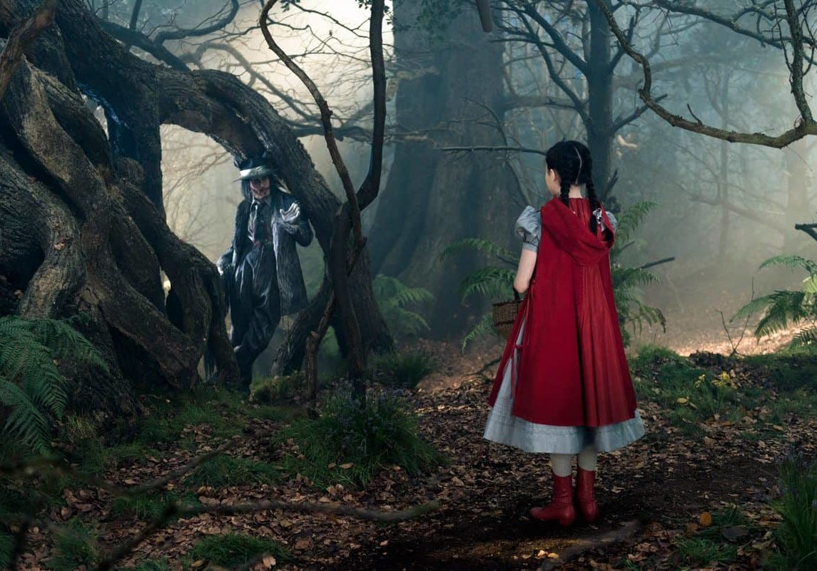 Johnny Depp as the Wolf and Lilla Crawford as Little Red Riding Hood in Disney's humorous and heartfelt musical INTO THE WOODS, directed by Rob Marshall and produced by John Deluca, Rob Marshall, Marc Platt and Callum McDougall.